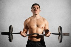 Sport, weightlifting, lifestyle and people concept. Confident sportsman with muscular body exercises in gym, lifts heavy weight, d. Emostrates naked torso abs Royalty Free Stock Images