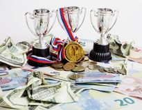 Sport winning concept: three cups among diverse currencies euro, Royalty Free Stock Image