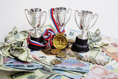 Sport winning concept: three cups among diverse currencies euro, dollar, rubl, gold medal first place Stock Images