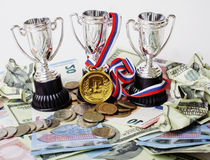 Sport winning concept: three cups among diverse currencies euro, dollar, rubl, gold medal first place. Close up Royalty Free Stock Photography