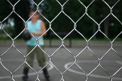 Sport Wire Netting Fence. Kid playing behind a Wire Netting Fence Royalty Free Stock Photos