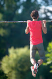 Sport woman athlete is Chin-ups and Pullups training on an abandoned sports field. Pull-up on the bar. Athlete Outdoors. royalty free stock image