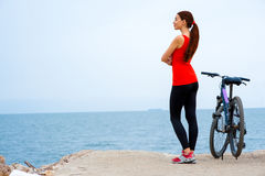 Sport woman with bicycle on the beach Royalty Free Stock Image