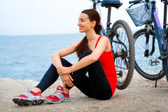 Sport woman with bicycles on the beach Stock Image