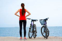 Sport woman with bicycles on the beach Royalty Free Stock Photo