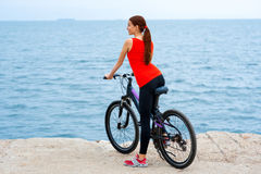 Sport woman with bicycles on the beach Royalty Free Stock Photos