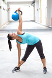 Sport woman in blue with blue dumb bell demonstrating the windmill pose Stock Images