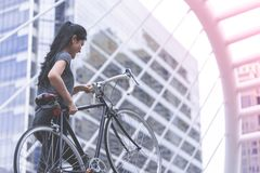 Sport woman carrying her bike up the stair stock photo