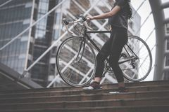 Sport woman carrying her bike up the stair stock image