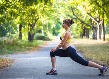 Sport woman doing exercises during outdoor cross training workout. Fitness model training outside in park Stock Photos
