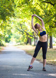Sport woman doing exercises during outdoor cross training workout. Fitness sport model summer training Stock Photography