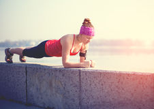 Sport woman doing plank outside in city quay. Sport fitness woman doing outdoor cross training workout Royalty Free Stock Image