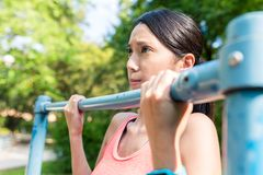 Sport Woman doing Pull up at green park. Asian young beautiful woman portrait royalty free stock photos