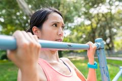 Sport Woman doing Pull up at park. Asian young beautiful woman portrait stock photos