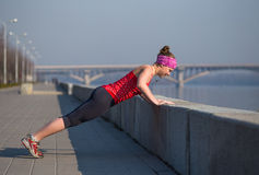 Sport woman doing push-ups outside on city quay in the morning Stock Photography