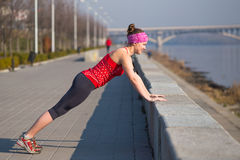 Sport woman doing push-ups during training outside in city quay early morning. Sport woman training outside in city quay early morning Royalty Free Stock Photo