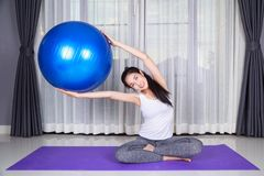 Woman doing yoga exercise with fitness ball Royalty Free Stock Photos