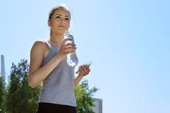 Sport woman drinking water and listening to music Royalty Free Stock Photos