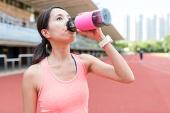 Sport woman drinking water in sport stadium. Asian young woman Royalty Free Stock Photography