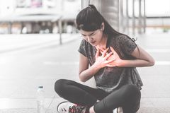 Sport woman having an injury on her heart chest disease attac royalty free stock photo