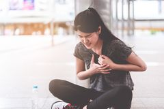 Sport woman having an injury on her heart chest disease attac royalty free stock images