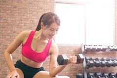 Sport woman with dumbbell. Sport woman hold dumbbell and training hard in the gym Stock Photo