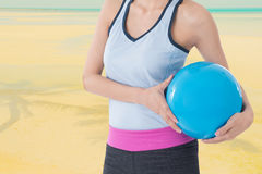 Sport woman holding beach ball with beach picture in background. Sport woman holding a beach ball with beach picture in background Royalty Free Stock Images