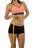 Sport woman holding measure tape showing slim perfect size abs and stomach Royalty Free Stock Photos