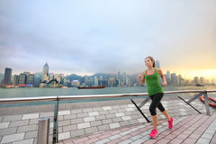 Sport woman jogging in Hong Kong city exercising. Sport woman runner running in Hong Kong skyline. Asian chinese fitness athlete jogging training living healthy Royalty Free Stock Images