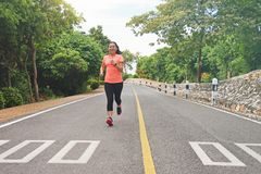 Sport woman jogging on the road in the park Stock Image