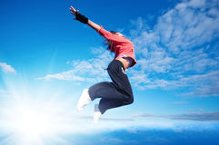 Sport woman jumping and fly over sky and sun Stock Photography