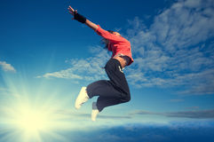 Sport woman jumping and fly over sky and sun. Beautiful sport woman in urban sportswear jumping and fly over blue sky with clouds and sun beam Stock Photography
