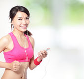 Sport woman listen music. Sport woman running and listen music with nature green background, model is a asian girl Royalty Free Stock Photography