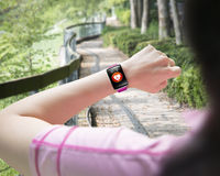 Sport woman looking at health sensor smart watch hand wearing. On forest trail background Royalty Free Stock Photo