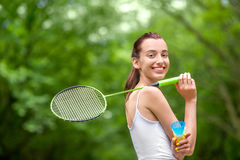 Sport woman playing badminton. Sport woman with badminton racket and shuttlecock in the park Stock Photos