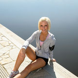 Sport woman relax on pier sitting water Royalty Free Stock Photos