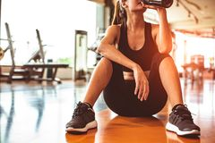 Sport Woman Relax Resting After Workout Or Exercise In Fitness Gym. Sitting And Drinking Protein Shake Or Drinking Water On Floor Royalty Free Stock Photo
