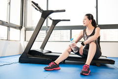 Sport woman rest on treadmill use smartwatch drinking water Stock Photography