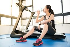 Sport woman rest on treadmill use smartwatch drinking water Royalty Free Stock Photography