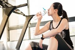 Sport woman rest on treadmill use smartwatch drinking water Royalty Free Stock Photos