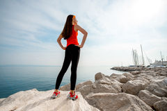 Sport woman on the rocky beach Royalty Free Stock Images