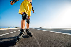 Sport woman with rollers on the highway Royalty Free Stock Photos