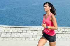 Sport woman running. With sea at background. She is smiling and  wears earphones Royalty Free Stock Images