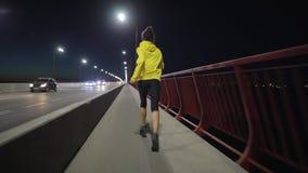Sport woman running along night bridge, rear view. Sport woman running along the night bridge, late training, rear view stock video