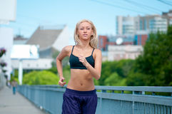 Sport woman running on city street Royalty Free Stock Images