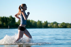 Sport woman running in cold water. Beautiful young sport woman running in water on sunny summer day Stock Photography