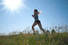 Sport woman running over green grass and sky Royalty Free Stock Photography