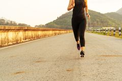 Sport woman running on a road. Fitness woman training at sunset royalty free stock image