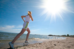 Sport woman running in sea coast Royalty Free Stock Photography