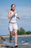 Sport woman running in sea coast Stock Image